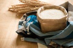 Ακατέργαστο σιτάρι ρυζιού και ξηρό φυτό ρυζιού στο ξύλινο επιτραπέζιο υπόβαθρο Στοκ Φωτογραφία
