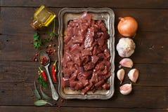Ακατέργαστο συκώτι βόειου κρέατος με τα καρυκεύματα, τα χορτάρια και τα λαχανικά Στοκ Εικόνα