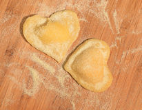 Ακατέργαστο χειροποίητο ravioli δύο με μορφή της καρδιάς, που καλύπτεται με το αλεύρι και που τοποθετείται στον ξύλινο πίνακα Στοκ φωτογραφία με δικαίωμα ελεύθερης χρήσης