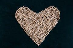 Ακατέργαστο chickpea με μορφή καρδιάς που απομονώνεται στο μαύρο bacground Οργανικός που αυξάνεται Ακατέργαστη πρωτεΐνη Υγιές συσ στοκ φωτογραφίες