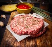 Ακατέργαστο cutlet για burger στον τέμνοντα πίνακα με τη σάλτσα, κρεμμύδια ξύλινο αγροτικό στενό σε επάνω υποβάθρου Στοκ εικόνες με δικαίωμα ελεύθερης χρήσης
