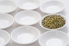 Ακατέργαστο mung φασόλι στα μικρά κύπελλα από την επανάληψη μορφής κύκλων στο λευκό Στοκ Εικόνες