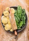Ακατέργαστο Tortellini με την κυλώντας καρφίτσα και φρέσκα φύλλα σπανακιού στο γκρίζο πιάτο στο ξύλινο υπόβαθρο με το αλεύρι σίτο στοκ εικόνες