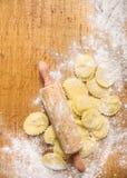 Ακατέργαστο Tortellini με την κυλώντας καρφίτσα στο ξύλινο υπόβαθρο με το αλεύρι σίτου Στοκ Εικόνες