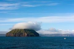 Ακατοίκητο νησί με ένα καπέλο των σύννεφων Στοκ Φωτογραφία