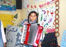 Ακκορντέον παιχνιδιού κοριτσιών στο στρατόπεδο στην Αίγυπτο Στοκ Εικόνες