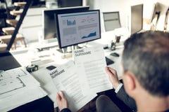Ακμάζων επιχειρηματίας που διαβάζει το βιογραφικό σημείωμα κατά τη διάρκεια της συνέντευξης στοκ εικόνα