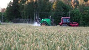 Ακολουθήστε τις οδηγώντας χημικές ουσίες ψεκασμού μηχανών τρακτέρ αγροτών στον τομέα δημητριακών το καλοκαίρι απόθεμα βίντεο