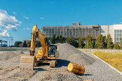 Ακολουθημένος εκσκαφέας σε ένα εργοτάξιο οικοδομής μεταξύ των σωρών της συντριμμένης πέτρας Στοκ Φωτογραφίες
