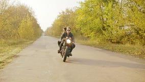 Ακολουθώντας πυροβολισμός της οδηγώντας μοτοσικλέτας ζευγών στο δασικό δρόμο το φθινόπωρο Ελκυστικός νεαρός άνδρας στα γυαλιά ηλί απόθεμα βίντεο