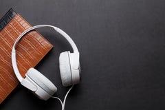 Ακουστικά και σημειωματάριο Στοκ Φωτογραφίες