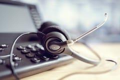 Ακουστικά και τηλέφωνο κασκών στο τηλεφωνικό κέντρο στοκ φωτογραφία με δικαίωμα ελεύθερης χρήσης