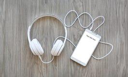 Ακουστικά και smartphone με τη λέξη ` το κείμενό σας εδώ ` στην άσπρη οθόνη Στοκ Φωτογραφίες