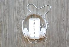 Ακουστικά και smartphone με τη λέξη ` το κείμενό σας εδώ ` στην άσπρη οθόνη Στοκ φωτογραφία με δικαίωμα ελεύθερης χρήσης