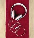 Ακουστικά σε ένα κόκκινα πλεκτά μαντίλι/ένα βούλωμα που αποσυνδέεται / Στενός-u Στοκ φωτογραφίες με δικαίωμα ελεύθερης χρήσης