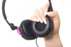 Ακουστικά σε ένα χέρι κοριτσιών Στοκ φωτογραφία με δικαίωμα ελεύθερης χρήσης