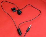 Ακουστικά στο κόκκινο - μουσική αγάπης Στοκ εικόνα με δικαίωμα ελεύθερης χρήσης