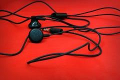 Ακουστικά στο κόκκινο υπόβαθρο Στοκ Εικόνες