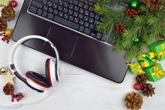 Ακουστικά, υπολογιστής και tinsel Χριστουγέννων Μελωδίες διακοπών Στοκ εικόνες με δικαίωμα ελεύθερης χρήσης