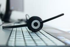 Ακουστικά υπολογιστών σε ένα πληκτρολόγιο του σημειωματάριου στοκ φωτογραφίες