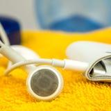 Ακουστικά, mp3 φορέας και πορτοκαλιά πετσέτα Στοκ Εικόνες