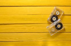 Ακουστικές κασέτες σε έναν κίτρινο ξύλινο πίνακα Αναδρομική τεχνολογία μέσων από 89s Τοπ όψη Στοκ φωτογραφία με δικαίωμα ελεύθερης χρήσης