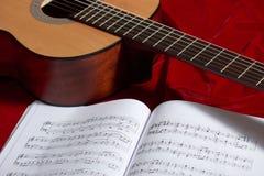 Ακουστικές σημειώσεις κιθάρων και μουσικής για το κόκκινο ύφασμα, στενή άποψη των αντικειμένων Στοκ Φωτογραφίες