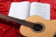 Ακουστικές σημειώσεις κιθάρων και μουσικής για το κόκκινο ύφασμα, στενή άποψη των αντικειμένων Στοκ Εικόνες