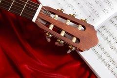 Ακουστικές σημειώσεις κιθάρων και μουσικής για το κόκκινο ύφασμα βελούδου, στενή άποψη των αντικειμένων Στοκ φωτογραφίες με δικαίωμα ελεύθερης χρήσης