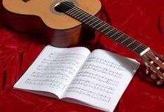 Ακουστικές σημειώσεις κιθάρων και μουσικής για το κόκκινο ύφασμα βελούδου, στενή άποψη των αντικειμένων Στοκ Φωτογραφίες