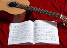 Ακουστικές σημειώσεις κιθάρων και μουσικής για το κόκκινο ύφασμα βελούδου, στενή άποψη των αντικειμένων Στοκ Εικόνα