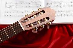 Ακουστικές σημειώσεις κιθάρων και μουσικής για το κόκκινο ύφασμα βελούδου, στενή άποψη των αντικειμένων Στοκ Φωτογραφία