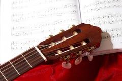 Ακουστικές σημειώσεις κιθάρων και μουσικής για το κόκκινο ύφασμα βελούδου, στενή άποψη των αντικειμένων Στοκ εικόνες με δικαίωμα ελεύθερης χρήσης
