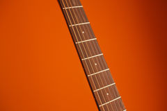 ακουστική κιθάρα έξι-σειράς σε ένα κόκκινο υπόβαθρο Στοκ Εικόνα