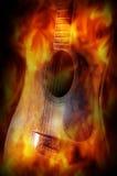 Ακουστική κιθάρα με την οθόνη φλογών πυρκαγιάς στοκ φωτογραφίες