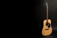 Ακουστική κιθάρα σε ένα μαύρο υπόβαθρο στη δεξιά πλευρά του πλαισίου, μισό-στροφή Όργανο Stringed Οριζόντιο πλαίσιο Στοκ Εικόνα