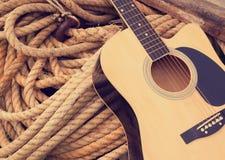 Ακουστική κιθάρα σε ένα τραχύ μπεζ υπόβαθρο σχοινιών Στοκ εικόνες με δικαίωμα ελεύθερης χρήσης