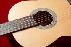 Ακουστική κιθάρα στο κόκκινο ύφασμα βελούδου, αντικείμενο κινηματογραφήσεων σε πρώτο πλάνο Στοκ εικόνα με δικαίωμα ελεύθερης χρήσης