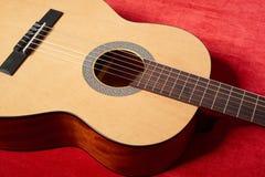 Ακουστική κιθάρα στο κόκκινο ύφασμα βελούδου, αντικείμενο κινηματογραφήσεων σε πρώτο πλάνο Στοκ Φωτογραφία
