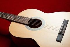 Ακουστική κιθάρα στο κόκκινο ύφασμα βελούδου, αντικείμενο κινηματογραφήσεων σε πρώτο πλάνο Στοκ Εικόνα