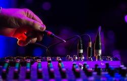 Ακουστική μουσική μιγμάτων του DJ αναμικτών του DJ γρύλων στην κονσόλα το χέρι του DJ s Στοκ Εικόνα