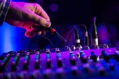 Ακουστική μουσική μιγμάτων του DJ αναμικτών του DJ γρύλων στην κονσόλα το χέρι του DJ s Στοκ Φωτογραφίες