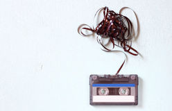 Ακουστική ταινία κασετών με την αφαιρεμένη έξω ταινία πέρα από τον μπλε κατασκευασμένο ξύλινο πίνακα Στοκ εικόνες με δικαίωμα ελεύθερης χρήσης