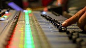 Ακουστικός μηχανικός που απασχολείται στον επαγγελματικό ακουστικό αναμίκτη στούντιο με τους μετρητές VU απόθεμα βίντεο