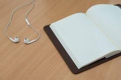 Ακουστικό και βιβλίο πέρα από τον ξύλινο πίνακα έτοιμος για το mockupe Στοκ Φωτογραφία
