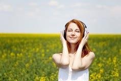 ακουστικό κοριτσιών πεδίων redhead Στοκ εικόνες με δικαίωμα ελεύθερης χρήσης