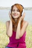 ακουστικό κοριτσιών redhead Στοκ Εικόνες
