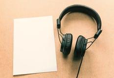 Ακουστικό με τη σημείωση της Λευκής Βίβλου για το ξύλινο γραφείο στο στούντιο μουσικής Στοκ Εικόνες