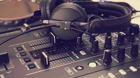 Ακουστικό στην κονσόλα μιγμάτων του DJ και τον αναμίκτη μουσικής στοκ φωτογραφία