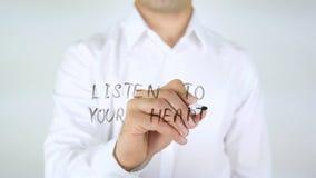 Ακούστε την καρδιά σας, άτομο που γράφει στο γυαλί στοκ φωτογραφία